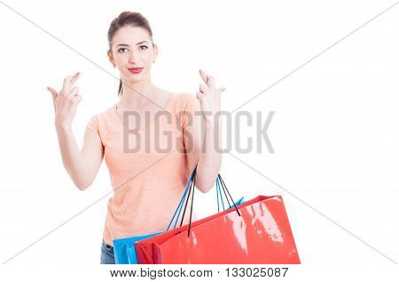 Shopping Concept With Woman Showing Fingers Crossed Holding Paper Bags