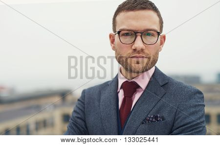 Serious intense young businessman with glasses standing outdoors on an open-air balcony staring at the camera head and shoulders with copy space