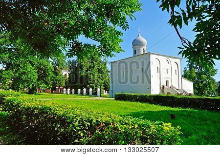 Assumption Church framed by greenery at the Yaroslav Courtyard in summer sunny day in Veliky Novgorod Russia