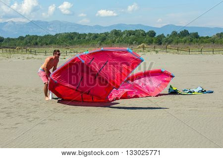 Kitesurfers on the beach prepare sport equipment for riding