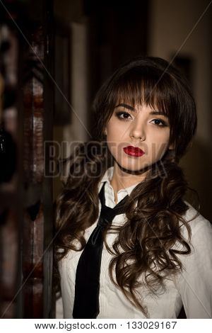 Portrait of beautiful, attractive, upset, serious, sad, nice, cute, lovely, unhappy, stressed, young, nice girl, model, student, school girl with red lips, white blouse, school uniform, tie, curly hair, ponytails in bar