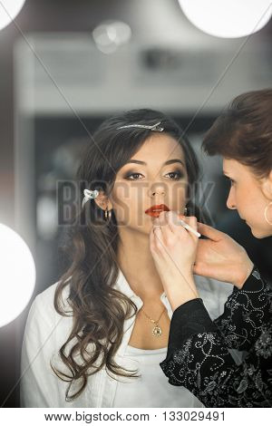 Professional make-up artist impose makeup on beautiful, attractive, adorable, stunning, excellent photo model, girl. Make up artist do a professional makeup, rouge with new, expensive, qualitative cosmetics.