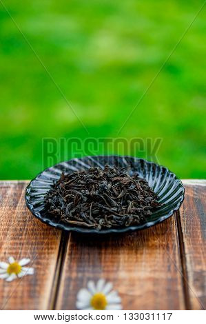 Dry Black tea on plate on wooden table with flowers of chamomile in garden and on nature background.Tea concept. Tea leaves. Closeup