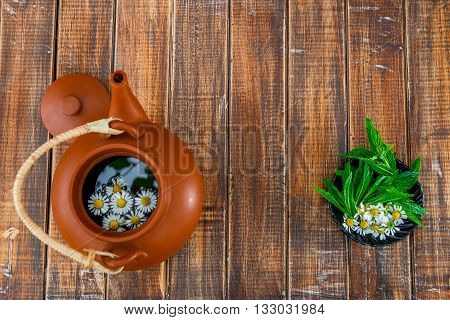 Open brown teapot with flower of chamomile near black plate with fresh mint and chamomile on wooden background. Frame. Copy space. Tea concept.