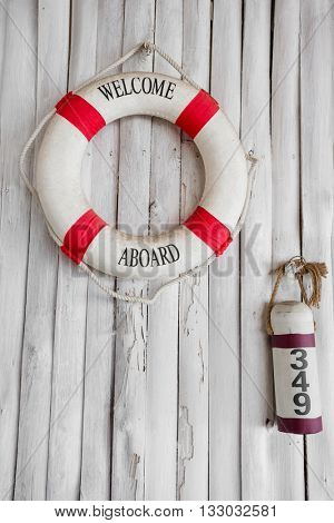 Composition on the marine theme with lifeline and buoy on old wooden background