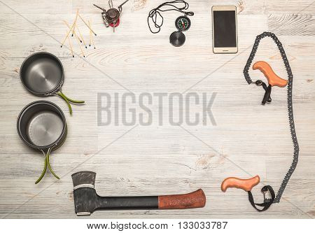 Hiking equipment: compass phone tent ax gas burner matches and other set on wooden background top view