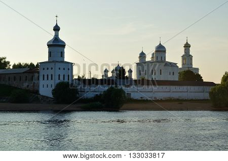 Architecture landscape - towers and cathedrals of Yuriev male monastery on the bank of the Volkhov river in Veliky Novgorod Russia sunset summer view in backlight