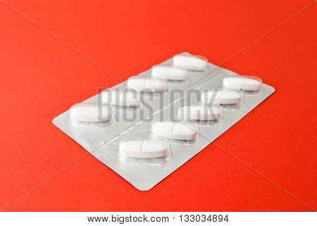 Silver packing of tablets on the red background