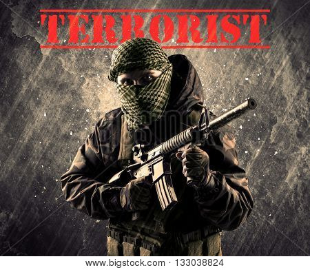 Portrait of dangerous masked and armed man with terrorist sign on grungy background