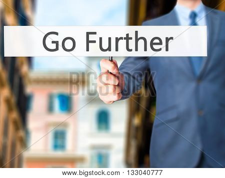 Go Further - Businessman Hand Holding Sign