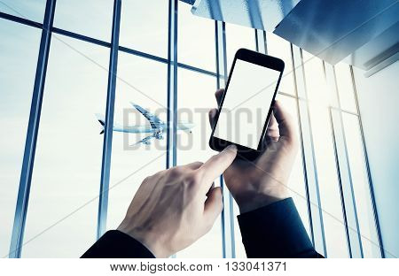 Photo businessman holding modern smartphone hand pushes button.Empty screen Isolated white, airplane take off, airport background. Ready for your private information.Business travel mockup.Horizontal