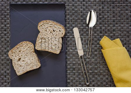 Black flat plate with two slices of bread and mustard yellow folded napkin spoon and knife aside on woven grey thick wire warp textured background