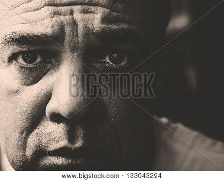 Close portrait up of a sad mature man. Monochrome photography