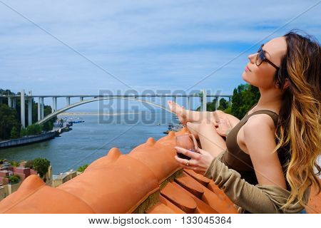 Woman enjoying sunbath with glass of port wine on the rooftop, on river bridge background.