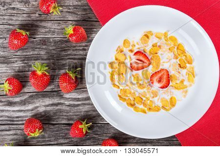 corn flakes with milk and strawberries in a white dish on a red table mat on an old rustic table studio lights top view