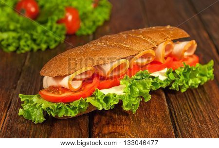 Long sandwich with lettuce slices of fresh tomatoes ham and cheese on a brown wooden table.