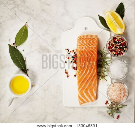 Delicious portion of fresh salmon fillet with aromatic herbs and spices - healthy food, diet or cooking concept. Top view.