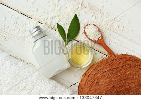 Coconut natural beauty treatment. Coconut oil, milk, dried shavings, nut, towel, skincare ingredients. Top view white wooden background.