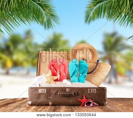 Old suitcase on tropical beach with palm leaves on background, travel concept