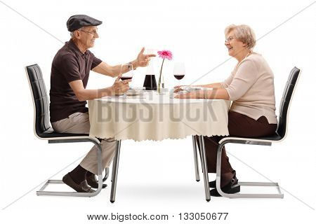 Mature couple talking to each other seated at a romantic table on a date isolated on white background