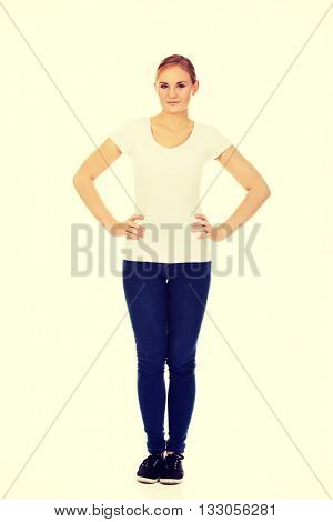Smiling young woman with hands on hips