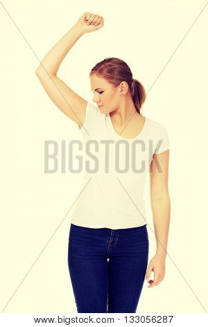 Young woman sniffing her armpit