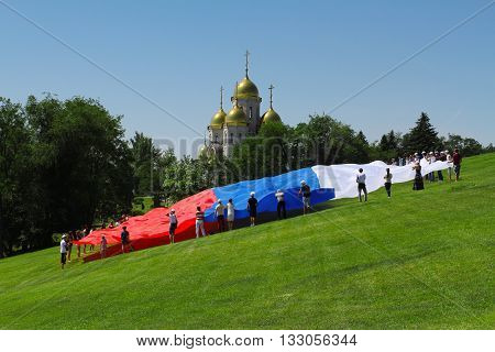 VOLGOGRAD, RUSSIA - JUNE 12, 2013: Activists unfurl a large flag of Russia the Day of Russia on the background of the Church of All Saints at Mamaev Kurgan in Volgograd