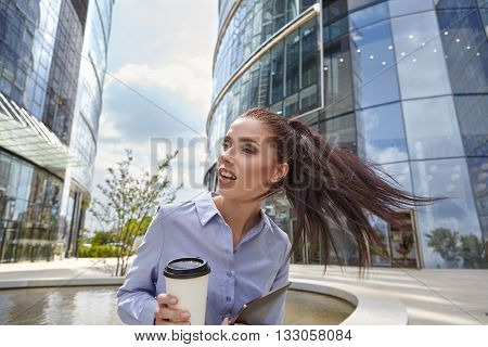 Good business talk. Cheerful young businesswoman talking on the mobile phone and holding cup of coffee while standing outdoors