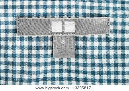Blank gray clothes label on blue plaid cloth as a background