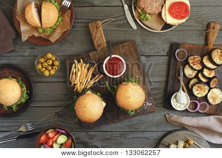 Different food on a wooden table burgers fries grilled eggplant salad different sauces and olives top view. Outdoors food Concept