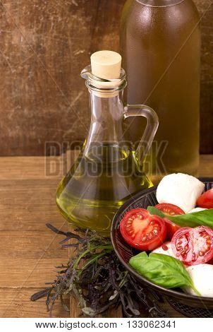 Tomato mozzarella basil leaves black olives and olive oil on wooden table.