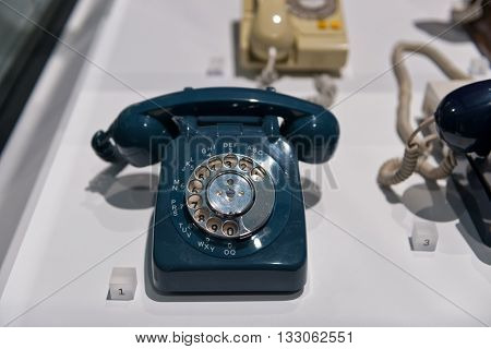SCIENCE MUSEUM, LONDON - FEBRUARY 08, 2016: Single vintage blue plastic and metal phone with rotary dial with other objects in telecommunications museum exhibit. London, UK on February 08, 2016.