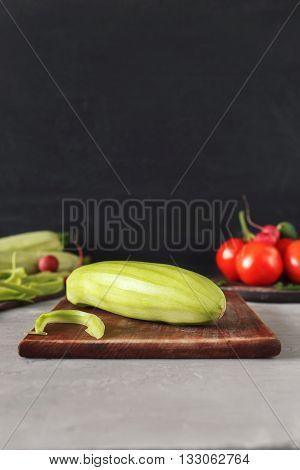 Marrow on a wooden cutting board closeup on a light table on a dark background with copy space. Cooking useful food