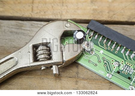 integrated computer circuit damaged with tools on a wooden table