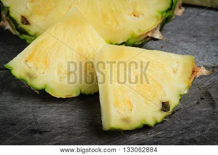 Pineapple chunks on gray wood background. Fresh pineapple.