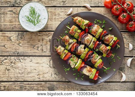 Turkey or chicken meat shish kebab skewers with tzatziki sauce, chopped parsley, garlic and tomatoes on rustic wooden table background. Traditional barbecue grill food