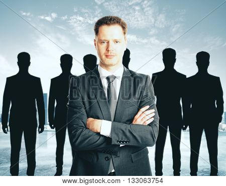 Leadership concept with handsome caucasian businessman in front of businesspeople silhouettes on abstract background