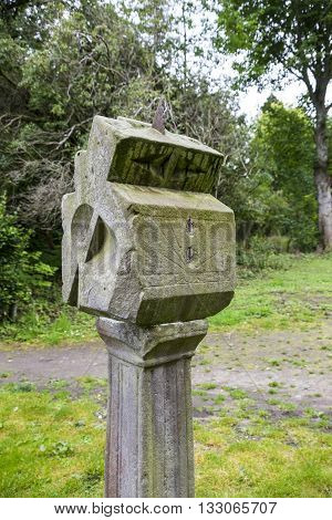 Old lichen covered stone sundial in the woods