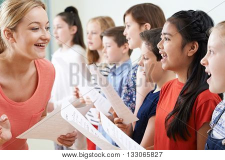 Group Of Children With Teacher Enjoying Singing Group