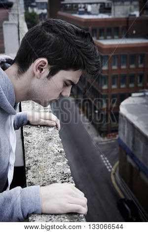 Depressed Young Man Contemplating Suicide On Top Of Tall Building
