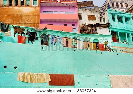 VARANASI, INDIA - JAN 1, 2016: Colored walls of rustic Indian homes of poor people with balconies and laundry drying on on January 1, 2016. Varanasi urban agglomeration had a popul. of 1435113.