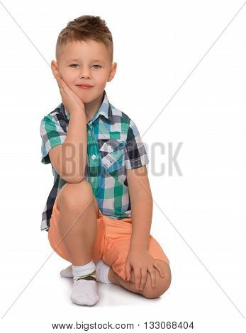 A little blond boy with a fashionable hairstyle on his head, a plaid shirt and orange shorts sat down on a knee - Isolated on white background