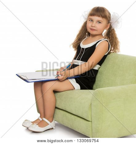Beautiful little girl diligent schoolgirl, sitting on the couch and makes an entry with a pen - Isolated on white background
