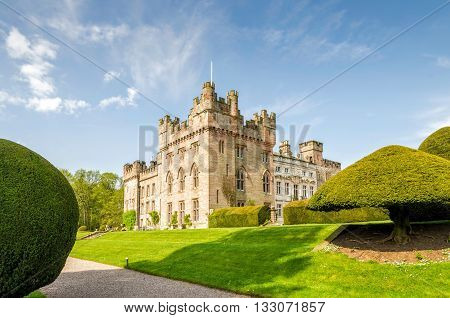 Manicured hedges and lawn on grounds of Hutton in the Forrest, Skelton, Cumbria, England on sunny day.