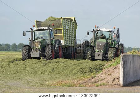 silage with two tractors and a car