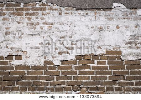 ancient texture of an old brown brick wall with destroyed plaster for background in vintage style and for old wallpaper