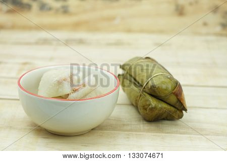 Bananas with Sticky Rice in small ceramic bowl on wooden background. Glutinous rice steamed in banana leaf. Traditional Thai food style Thai name is Khao Tom Mat.