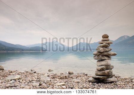 Balanced Stone Pyramide On Shore, Blue Water Of Mountain Lake.