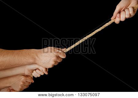 People hands pulling the rope on black background