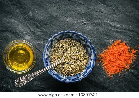 Mixture of spices chilli olive oil Giros on a black slate horizontal